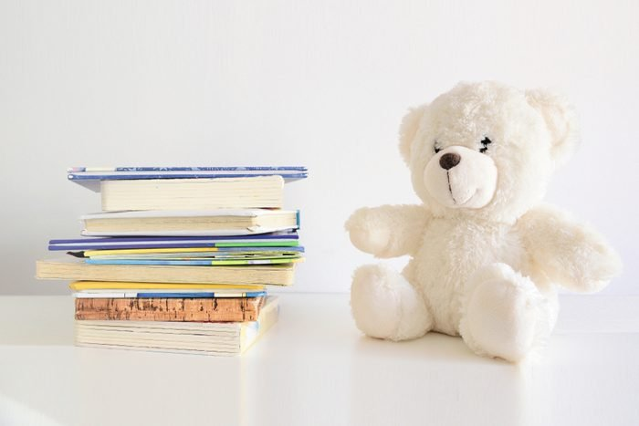 Some books in a pile and a teddy bear on it. Bookshelf in a child bedroom. Empty copy space for Editor's text.