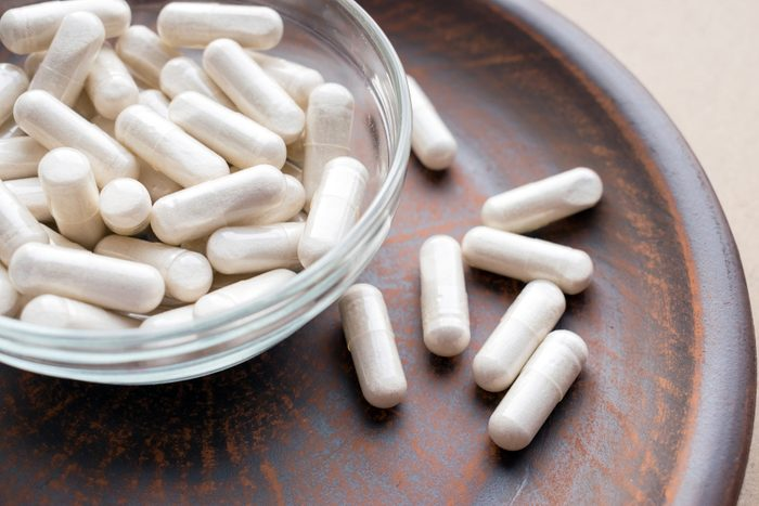 Veg herb capsules on round clay brown plate. Herbal Supplements Dangerous with Prescription Drugs. Dietary supplements, vitamins and minerals for vegans and vegetarians. Healthy lifestyle