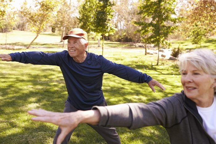Senior Couple Doing Tai Chi Exercises Together In Park