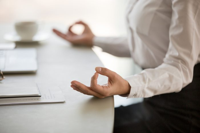 Office meditation for reducing work stress relief concept, female hands in mudra close up view, business woman practicing yoga at workplace for mindfulness development. mental health and balance