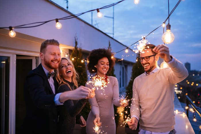Friends enjoying a rooftop party and dancing with sparklers in hands.