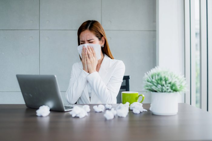 office syndrome allergy with business woman sick and sneeze with tissue and fever