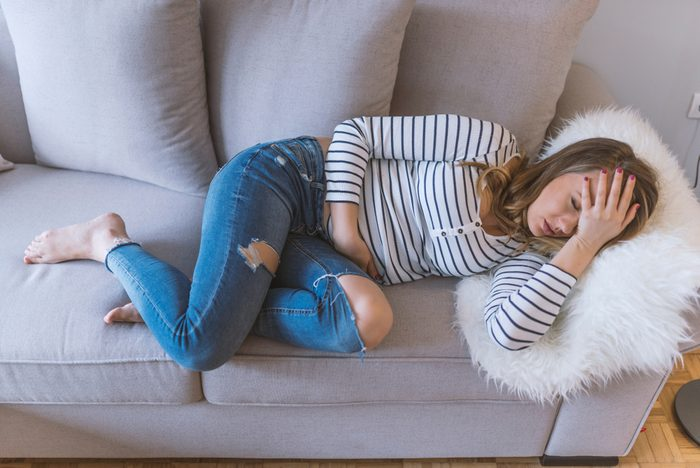 Young beautiful woman having painful stomachache. Woman with menstrual pain is holding her aching belly - body pain concept. woman having abdominal pain, upset stomach or menstrual cramps.