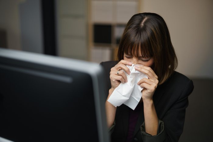 Woman sitting at a computer in an office, blowing her nose into a tissue