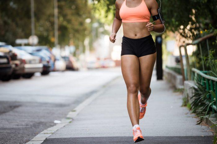 Runner listening to music while jogging on sidewalk.