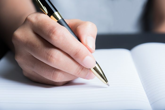 Business man Hands with pen writing on paper in close up view