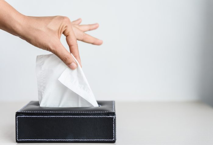 Woman hand picking white tissue paper from tissue box.