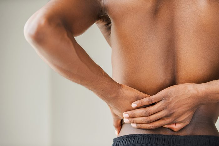Pain in back. Cropped image of young African man touching his back