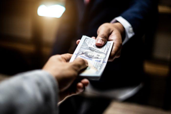 handing money to businessman close up