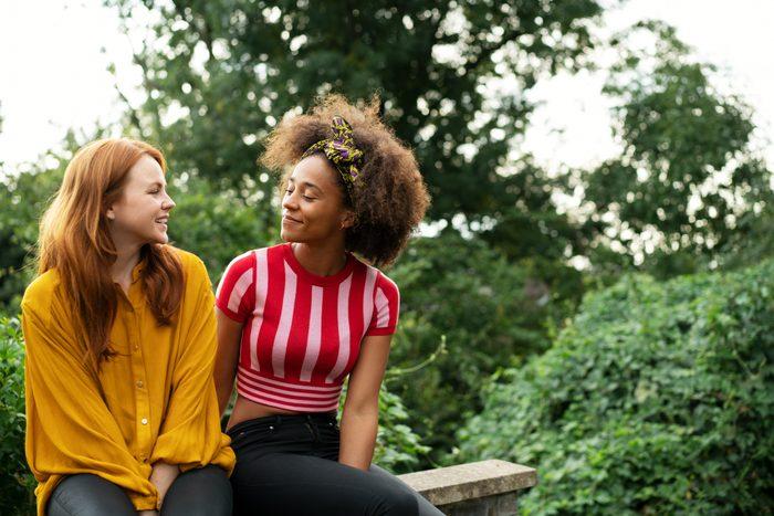 two young women talking outside