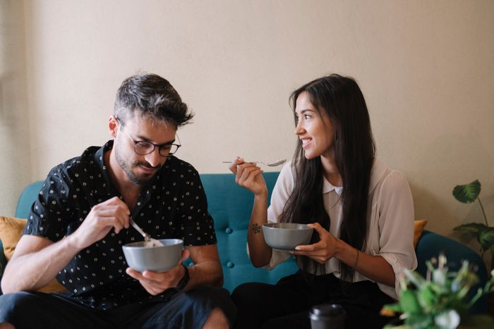 couple sitting on couch eating breakfast