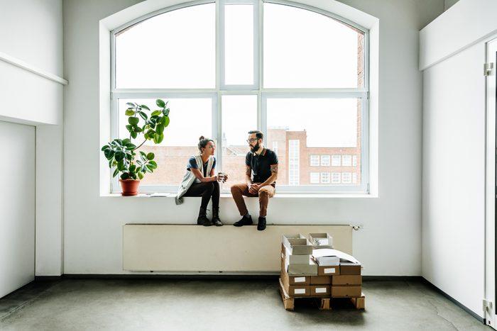 two people talking in empty room by the window