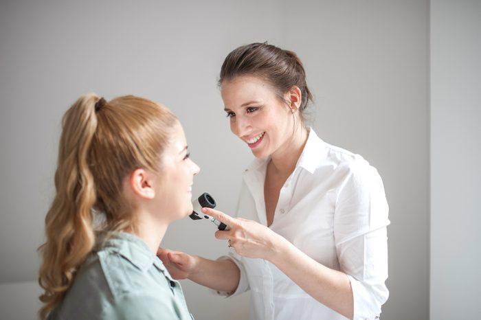 dermatologist inspecting patient's skin