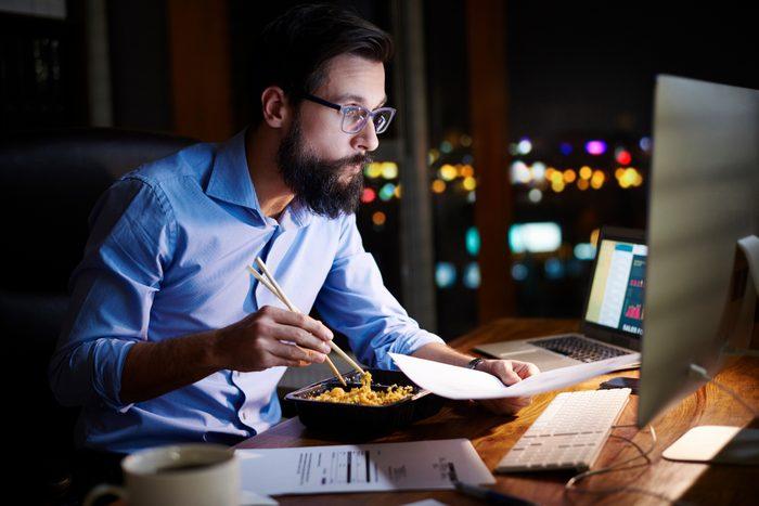 man eating dinner at night while working