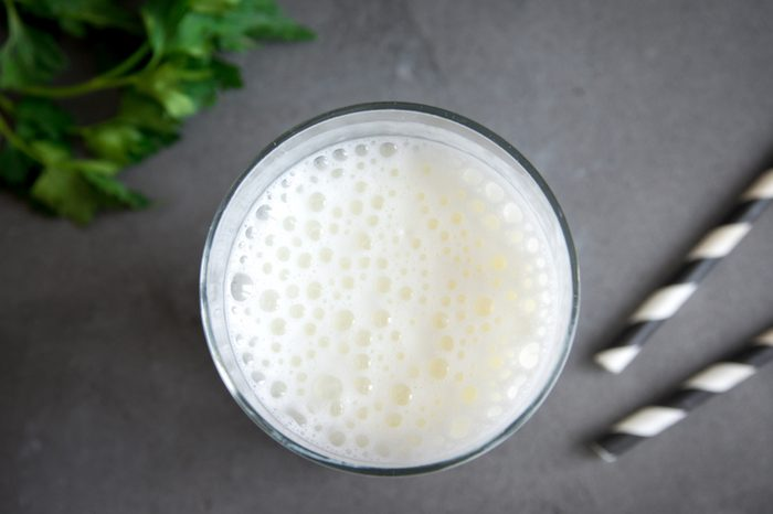Fresh plain homemade yougurt (yogurt, youghurt, kefir, ayran, lassi) in glass with herbs over gray background, copy space. Probiotic cold fermented dairy drink.