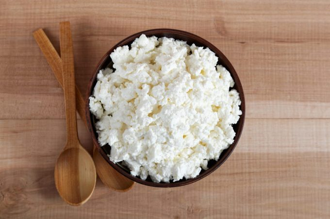 Fresh cottage cheese in a bowl with spoon on a wooden table.