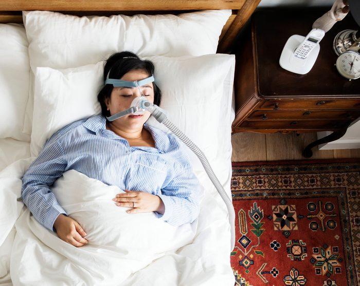 Woman sleeping with an anti-snoring mask