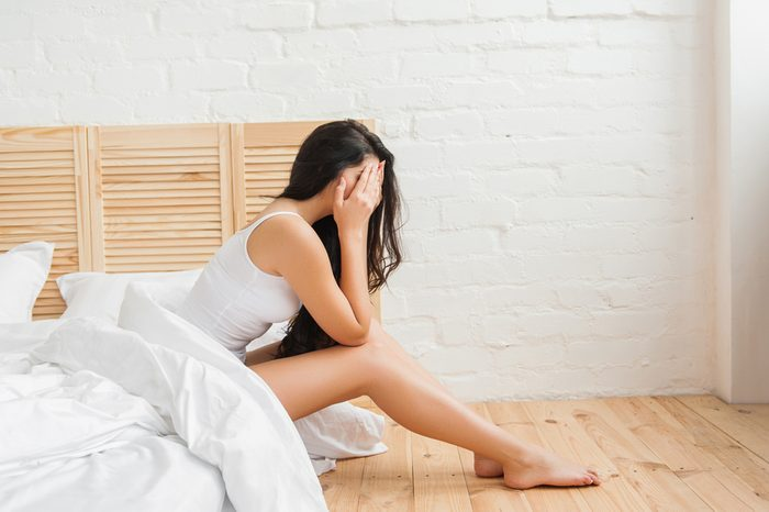 woman covering her face with hands while sitting in bed