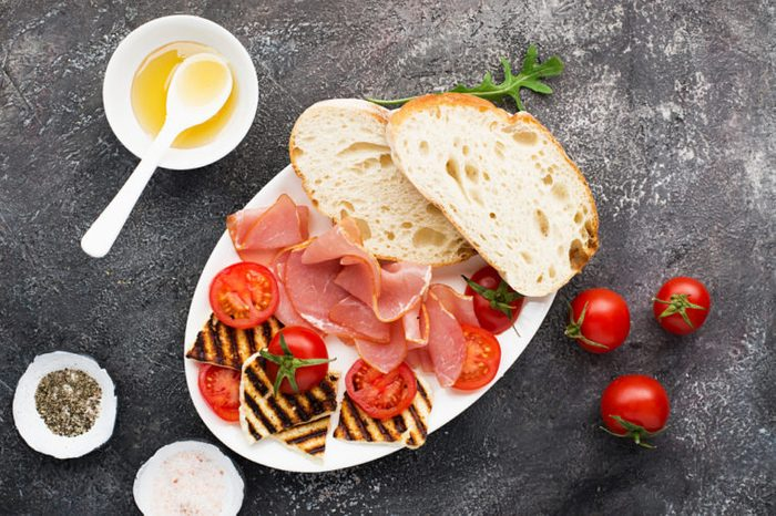 Halloumi cheese with bruschetta, tomatoes, prosciutto, honey, pine nuts on a plate