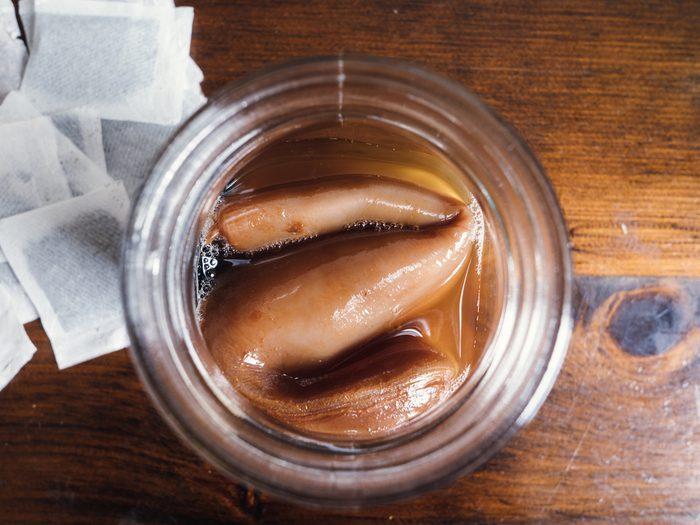 Jar of starter tea for Kombucha tea. SCOBY with tea bags on rustic wood table. Closeup.