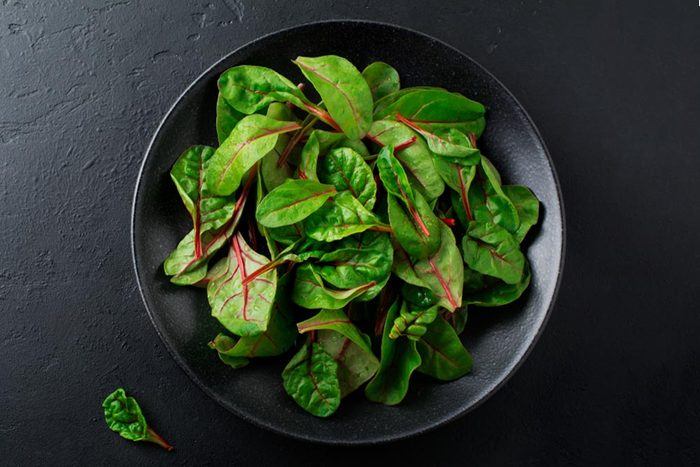 Fresh young leaves of chard for salad in a dark ceramic dish on black concrete background. Selective focus. Copy space. Top view.