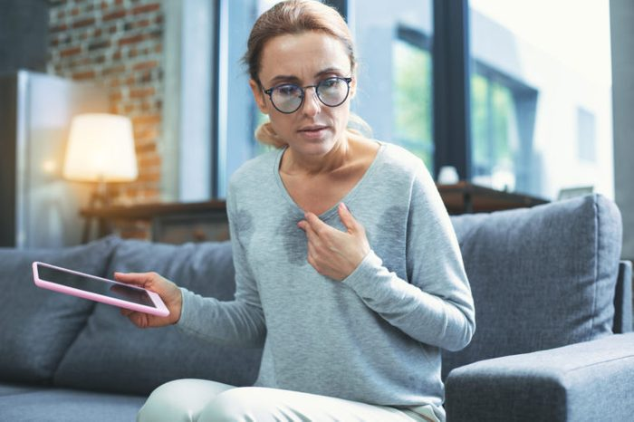 middle aged woman having hot flash sweating with tablet