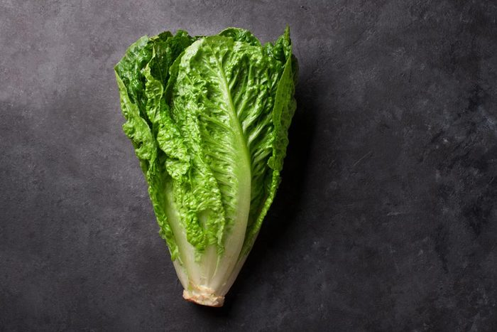Romaine lettuce salad over stone table. Top view with copy space
