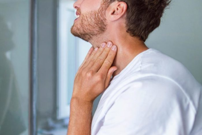 bearded man feeling his neck while looking in the mirror