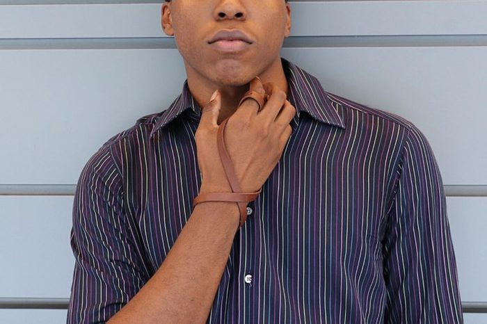 black man putting his hand to his throat