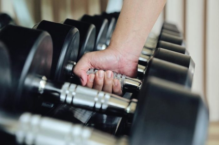 person grabbing a dumbbell