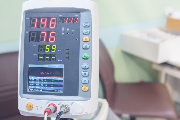 A Hospital Vital Sign Monitor on Trolley with Blood Pressure Cuff and Thermometer on hospital background.