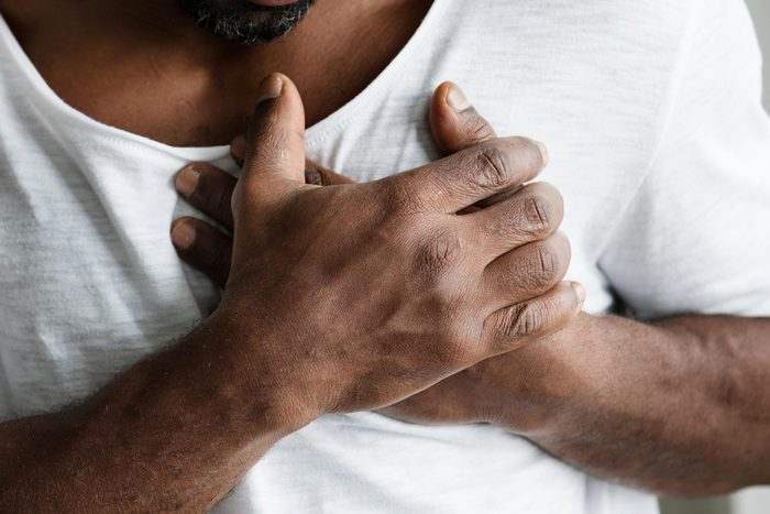 man with hands on heart; chest pain