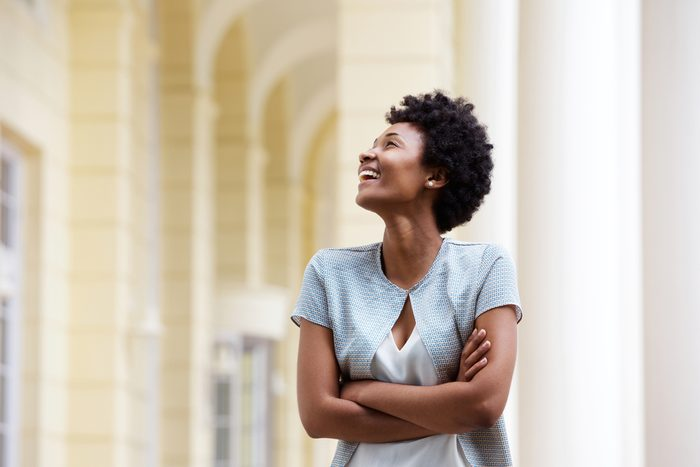 Portrait of a smiling young african woman standing outdoors with her arms crossed and looking away