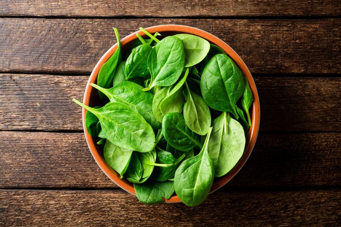 Fresh spinach leaves in bowl on rustic wooden table. Top view.