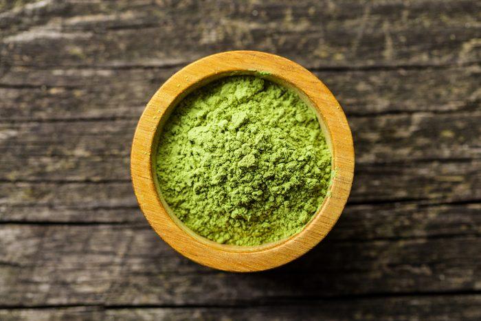 Green matcha tea powder in bowl. Top view.