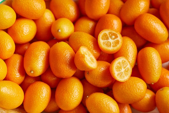 Top view of bunch of fresh kumquats in the organic food market. Some kumquats is cutted