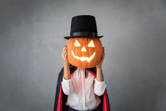 Funny child dressed Halloween costume. Kid painted terrible vampire. Autumn holiday concept