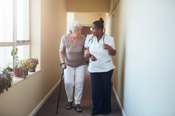 Senior woman with walking stick being helped by a female nurse at home. Full length shot of female doctor with elderly patient at nursing home.