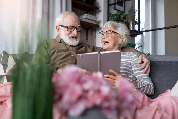 Pleasant memories. Portrait of old charming couple remembering sweet moments. Woman is looking at husband while laughing. Man is regarding at picture while tenderly cuddling wife