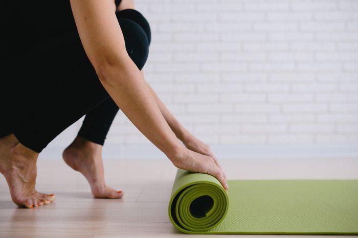 Woman rolling her green mat after a yoga class