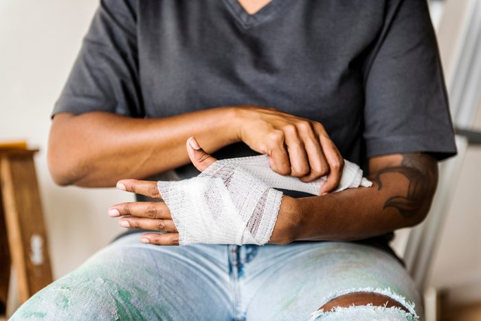 Man wrapping hand in gauze