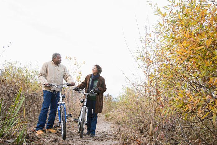 Couple pushing bicycles