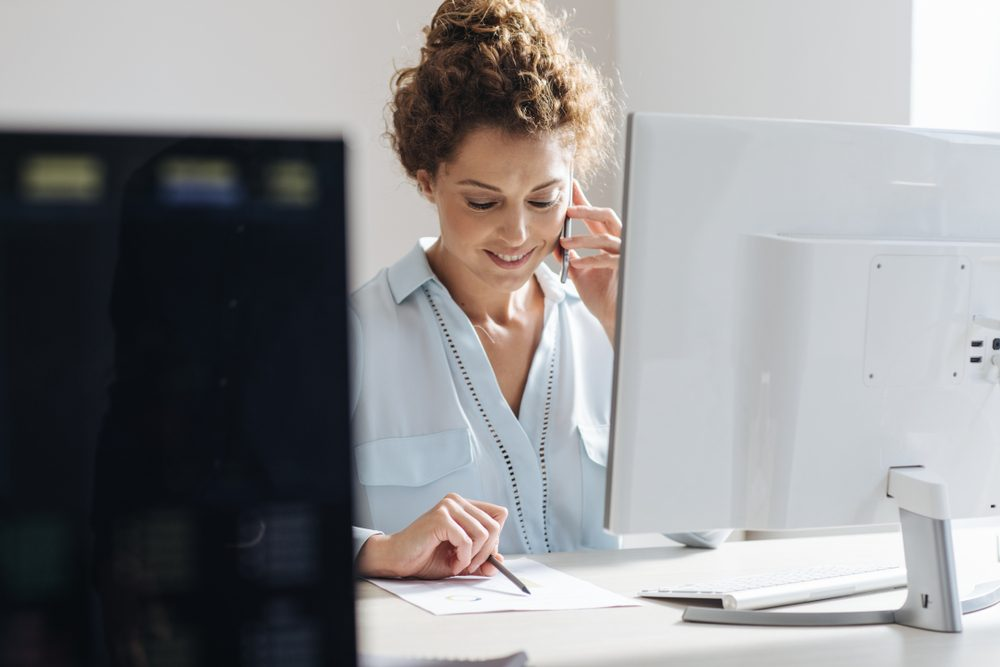 Young businesswoman using a mobile phone while working on a desktop computer