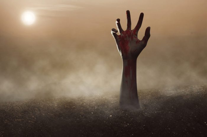 Zombie hand reaching out of the ground