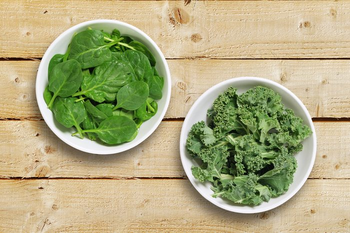 Two white bowls one containing spinach leaves and one containing chopped kale leaves