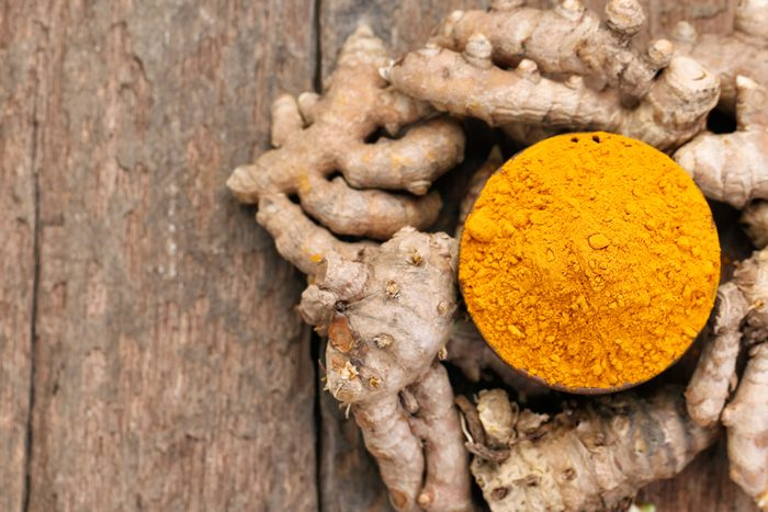 bowl of turmeric powder surrounded by turmeric root