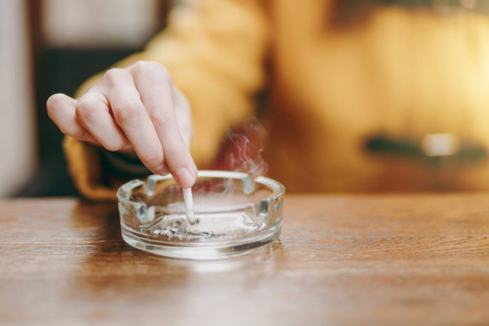 Focus on caucasian young woman hand putting out cigarette on glass ashtray on wooden table, cigarette butt, smoking is dying. Quit smoking. Health concept. Close up photo