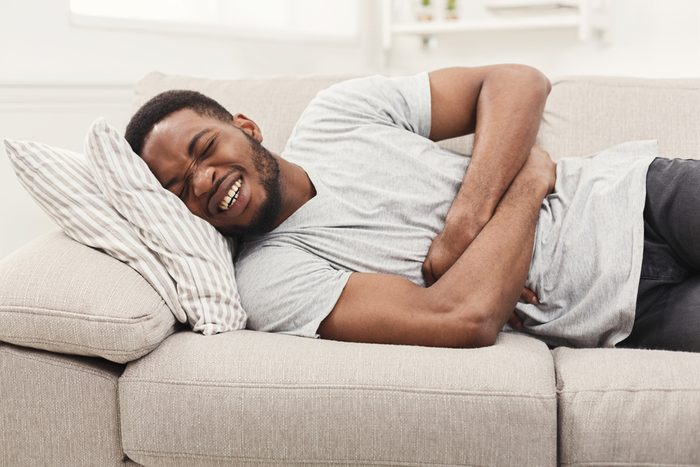 Handsome young african-american man suffering from stomach ache while lying on sofa at home