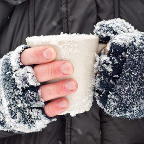 Frozen hands holding a mug