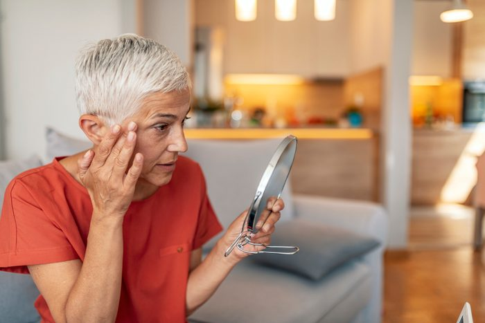 mature woman looking at her face in mirror